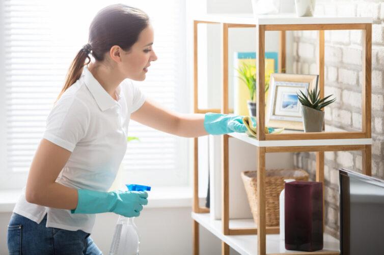 Women dusting shelf