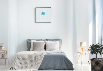 White and grey bedroom with wall art above the bed