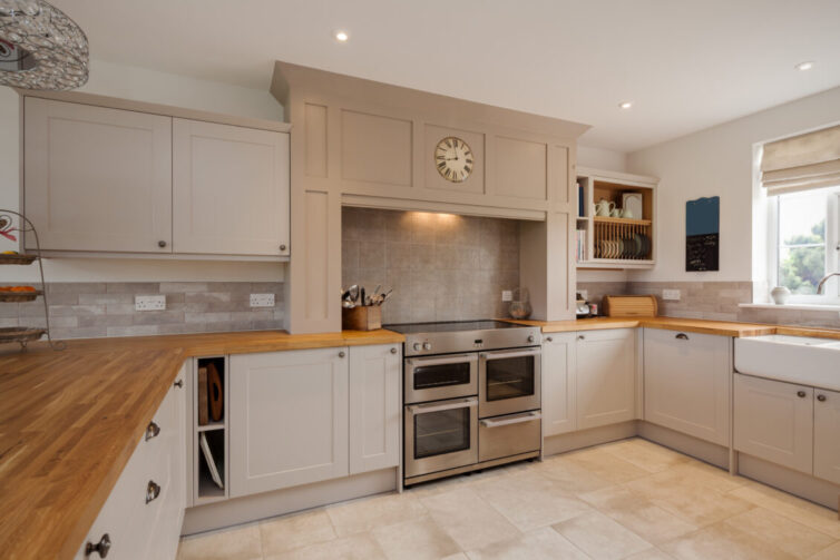 Modern Shaker style kitchen interior with fitted appliances including oak strip countertops and worksurfaces, cupboards and drawers
