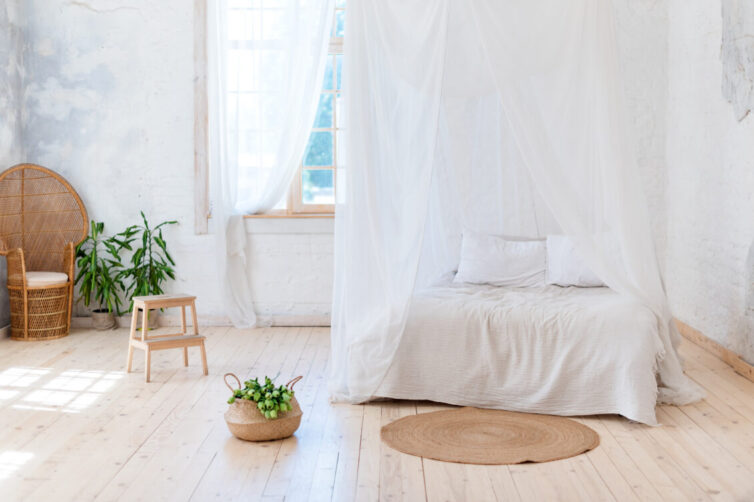 Tropical calm bedroom with four poster bed and draps. With wicker furniture and plants