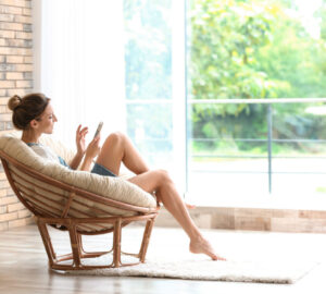 Young woman with mobile phone sitting in papasan chair near window at home