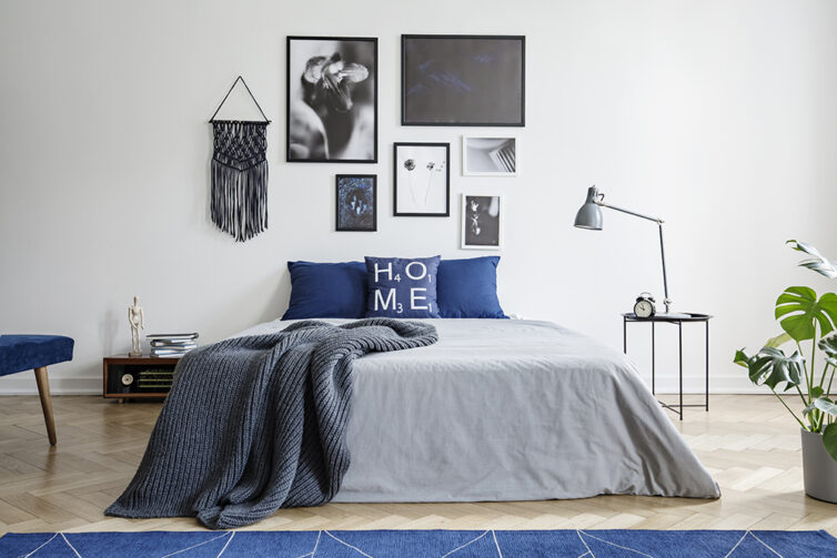 Blue and grey bedroom with black and white artwork on the wall