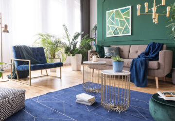 Green and blue tropical living room with plants and brass