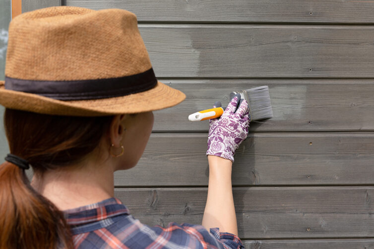 Women wearing hat, painting wood with grey paint