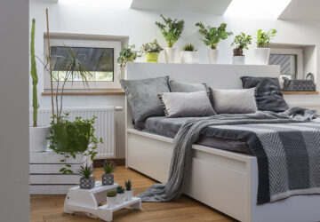 White bed and bedroom with house plants and grey bedding