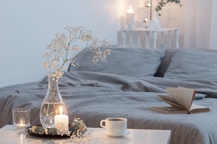 Peacefull bedroom with grey bedding, candle light and vase of flowers