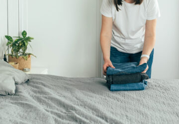 Woman folding clothes/ jeans in clutter free bedroom