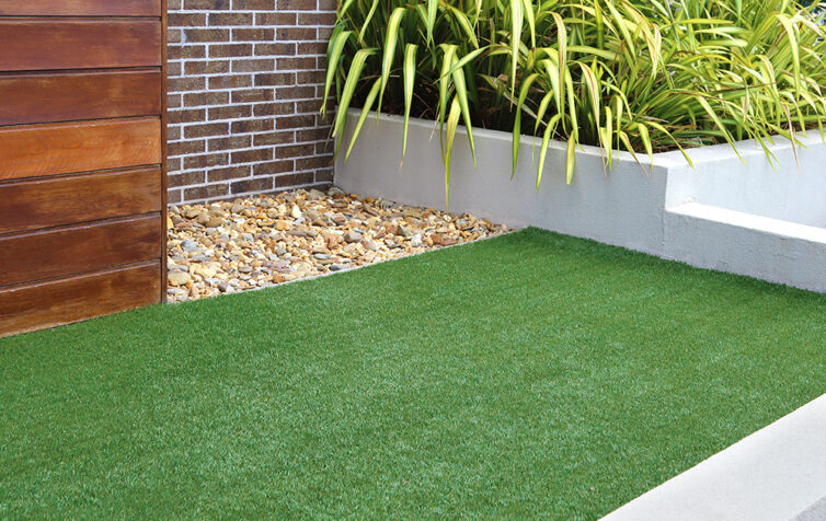 Artificial grass in modern garden with raised beds