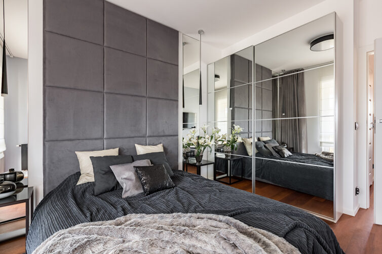 Grey and white modern bedroom with glass wadrobe