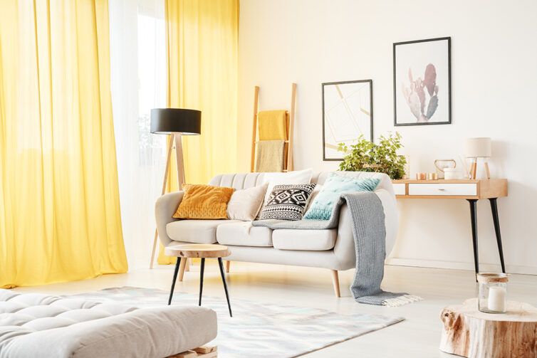 Bright fresh looking living room with yellow curtains white sofa and decorated with throws and cushions
