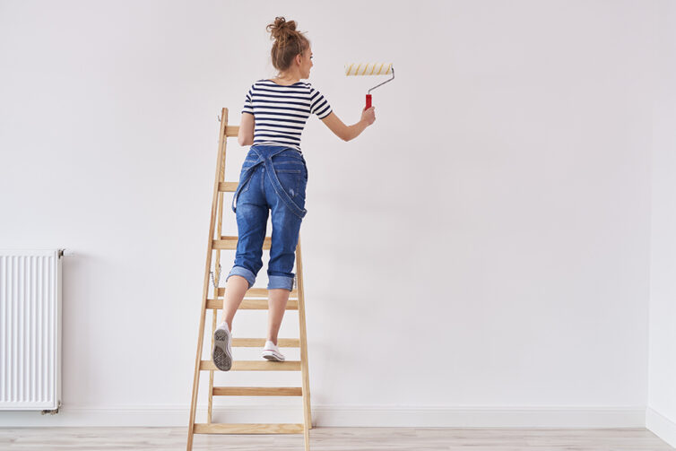 Women on a wooden step ladder painting wall