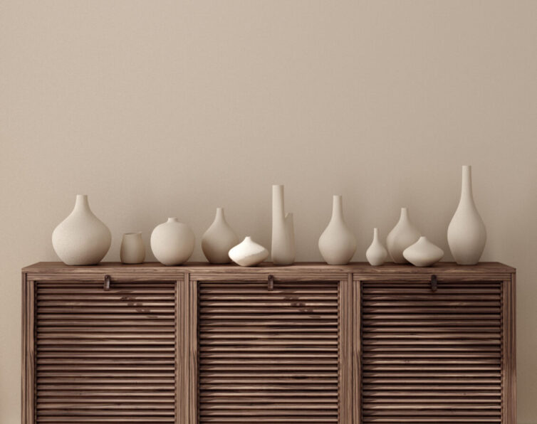 Light brown painted walls with brown wooden furniture covered in cream vases