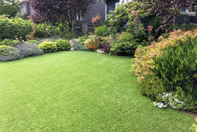 artificial lawn in the front yard with nice flowers and shrubs surrounding it