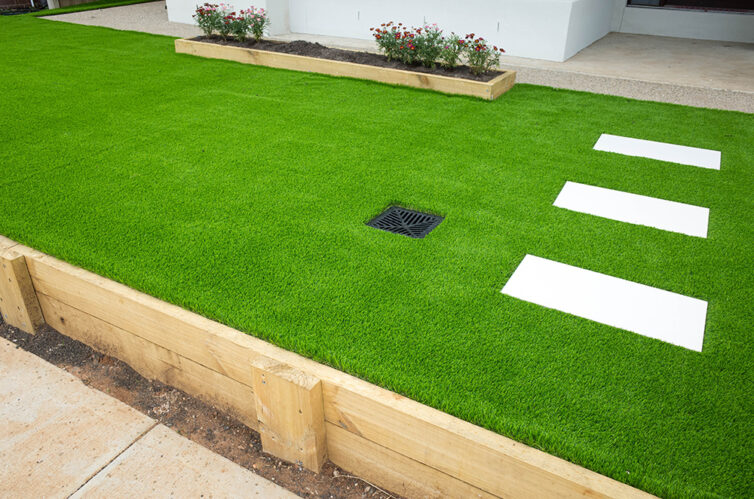 Artificial grass with concrete pathing slabs