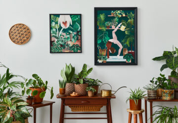 Living room with vintage retro shelf and tables with house plants, cacti. Yoga posta poster framed on the white wall.