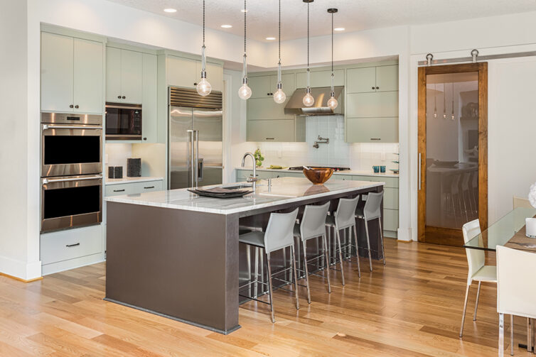 Modern kitchen with stainless steel appliances and laminate flooring