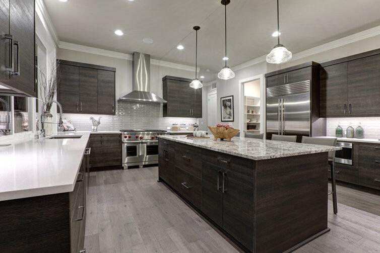 Grey laminate flooring with dark kitchen cupboards and white quartz countertops