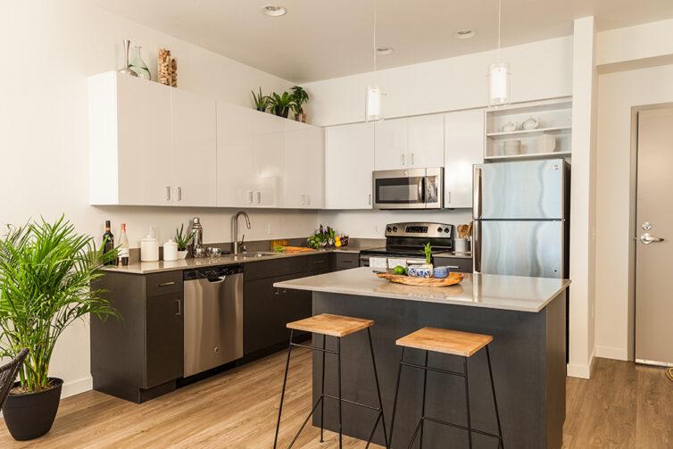 Modern dark kitchen cabinets with laminate flooring, bar stools and white worktops