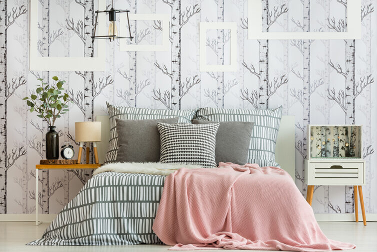 Bedroom decorated with pillows, sheets and wallpaper