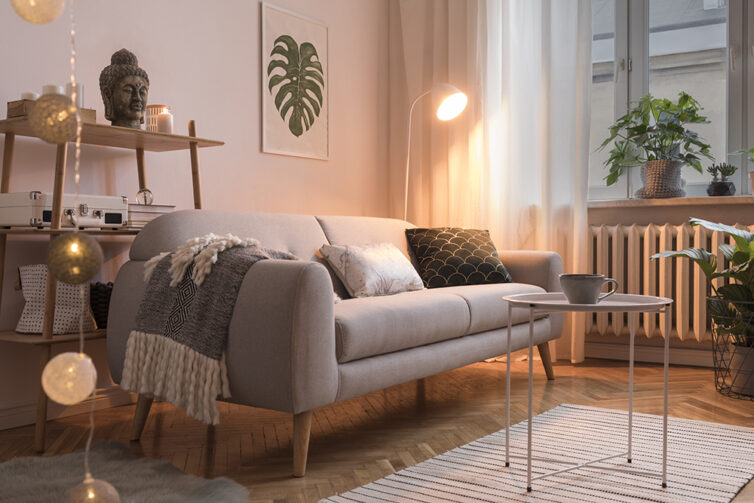 Cosy lounge with grey sofa, cushions, drapped blanket, and warm lighting