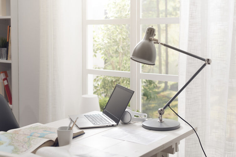 Bright well lite office with french doors, laptop, desk and desk lamp.