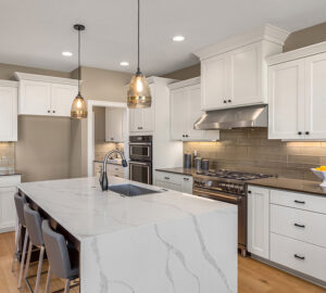 White kitchen cupboards with quartz counter tops and laminate flooring
