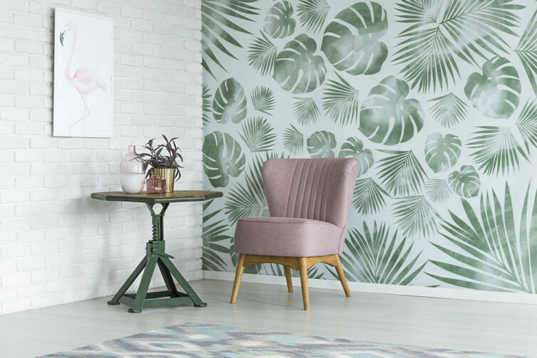 Green plant wallpaper with greyish pink slipper chair