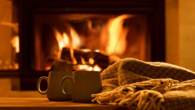 Mugs of hot chocolate by the woodburning fireplace