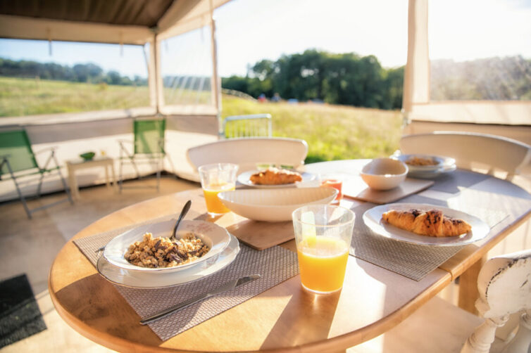 Glamping in large tent Breakfast table set and laid with bowls of cereal and a glass of orange fruit juice.