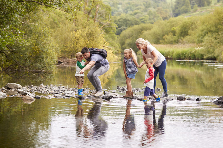 Family on holiday in the Lake District UK. Family crossing river via rocks in the water