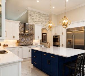 Modern White Kitchen in Estate Home. Blue kitchen island. White stone countertops
