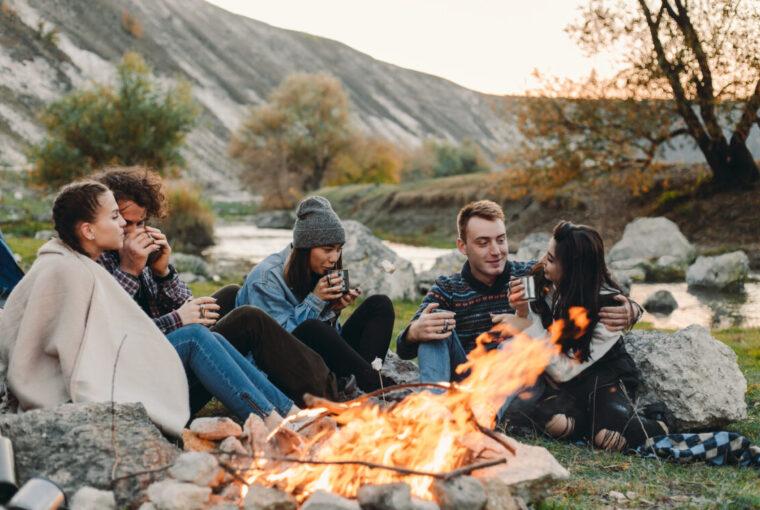 Group sat around bonfire drinking hot drinks.