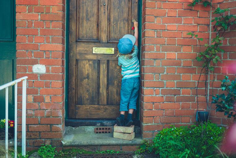 Child standing on bricks to unlock front door
