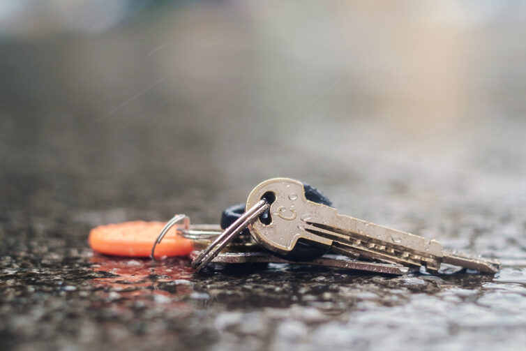 Wet pavement with set of lost keys on the ground