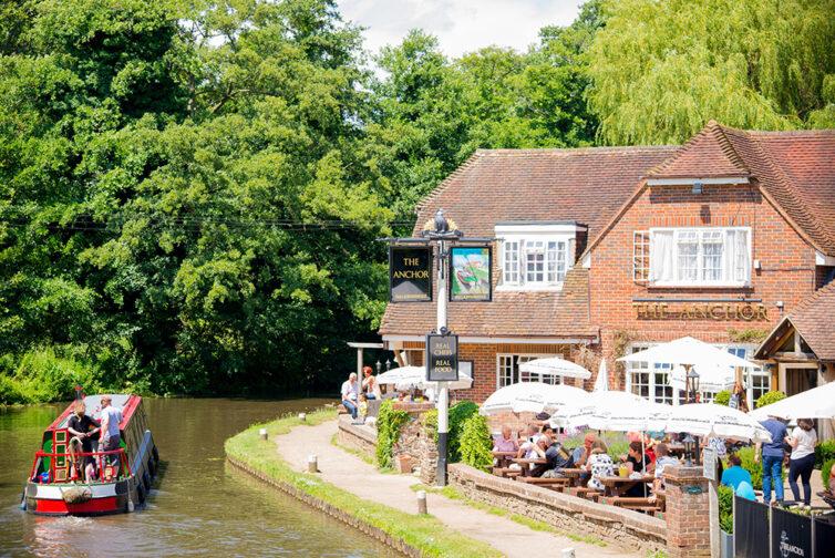 Narrow boat passes English pub on canal