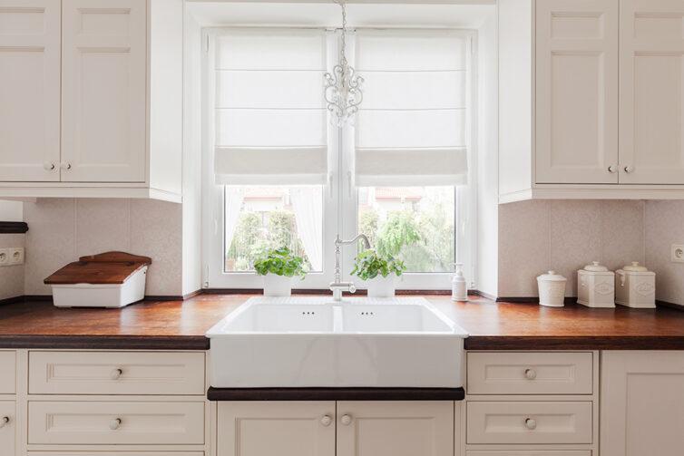 Large double white porcelain kitchen sink. Dark wood kitchen worktops and cream kitchen cupboards