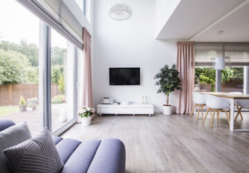 Contempory minimalist living room and open planed kitchen with grey laminate flooring