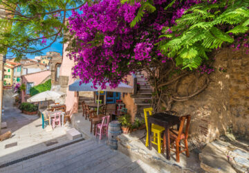 Street with cafe table and chairs. Flowers in bloom in Capoliveri village in Elba island, Tuscany, Italy, Europe