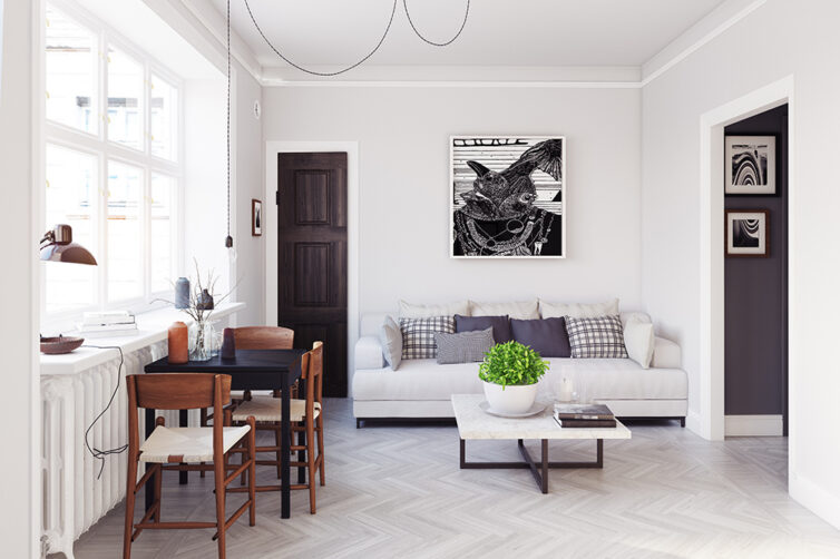 Small apartment with sofa and small dining table. Flooring covered in grey herringbone laminate