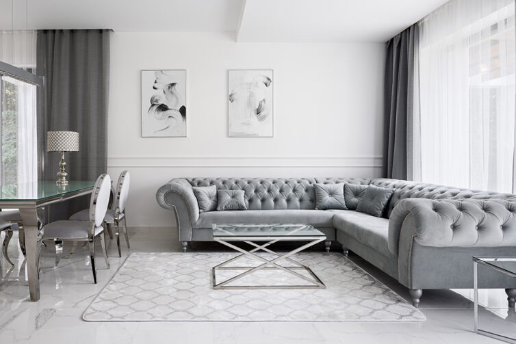 Minimalist opulent living room. Large chesterfield silver corner sofa, glass coffee table and dining table